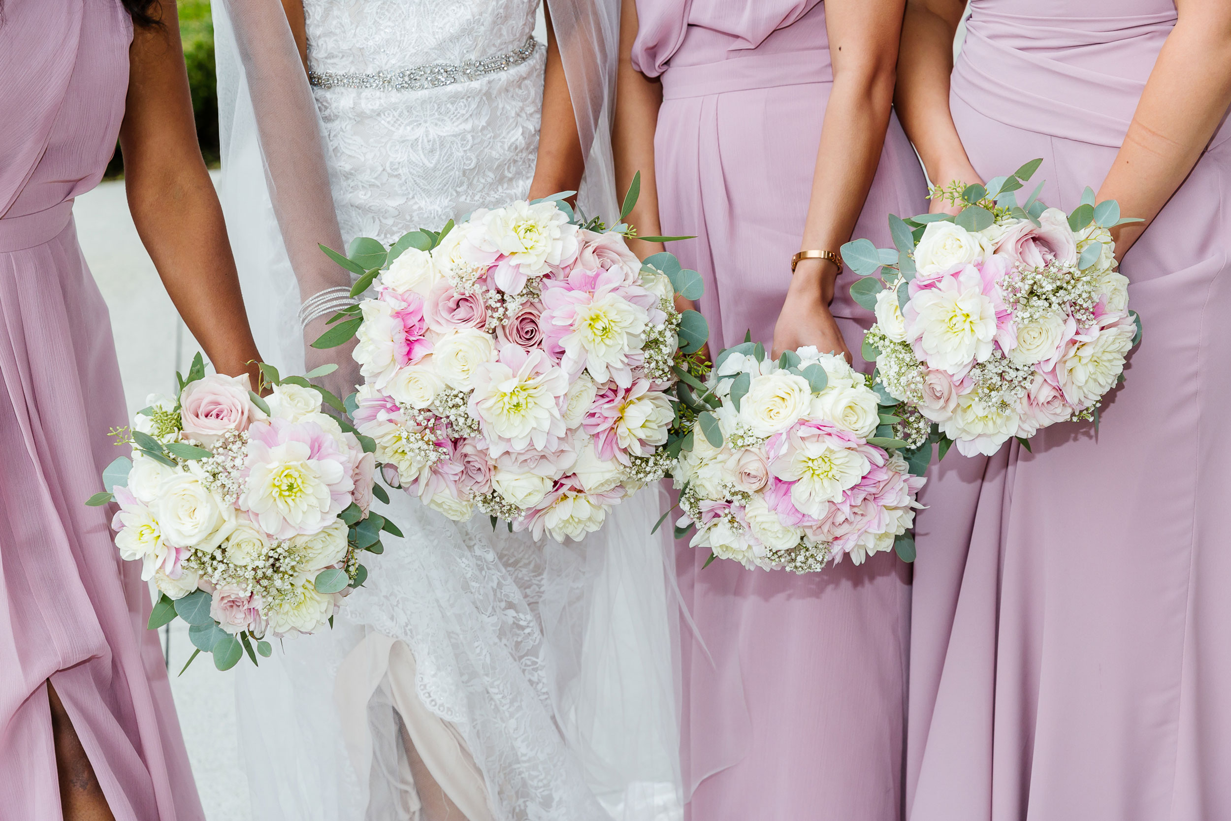 Spring floral bouquets held by bride and bridesmaid during wedding ceremony at Newlands
